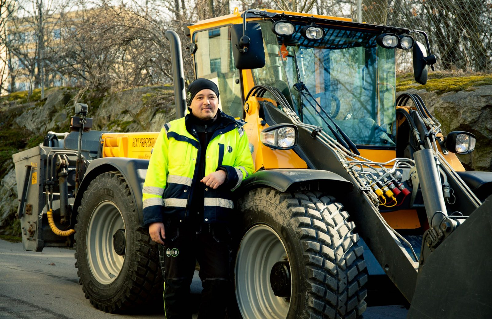 en man står vid en gul traktor
